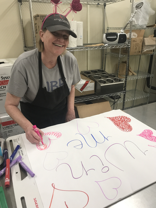 Theresa Adams making the sign for the giveaway